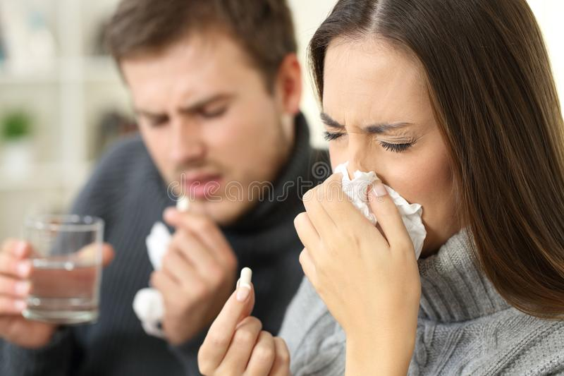 Άρρωστο ζεύγος που βήχει και που παίρνει τα χάπια στοκ φωτογραφίες με δικαίωμα ελεύθερης χρήσης