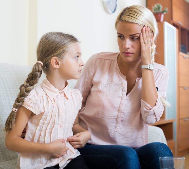 Άρρωστο κορίτσι με τον πόνο στο στομάχι και την ανησυχημένη μητέρα στο εσωτερικό στοκ εικόνες