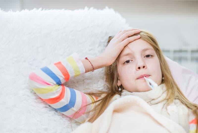 Άρρωστο κορίτσι με το θερμόμετρο στο στόμα σχετικά με το μέτωπό της στοκ φωτογραφία με δικαίωμα ελεύθερης χρήσης