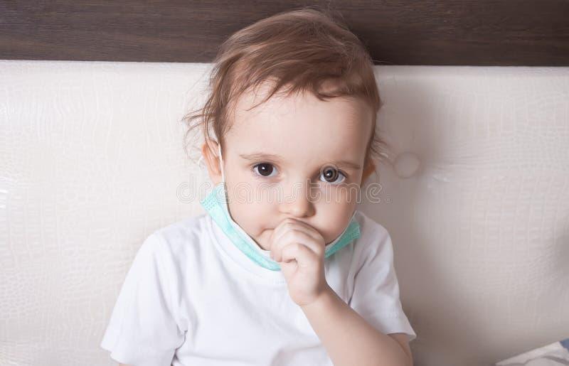 Άρρωστο μικρό κορίτσι που πάσχει από το βήχα στο κρεβάτι στο σπίτι στοκ φωτογραφία
