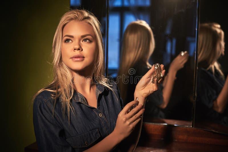 Άρωμα ένδυσης γυναικών στο αναδρομικό μπουκάλι του αρώματος στον κονσόλα-καθρέφτη στοκ φωτογραφία με δικαίωμα ελεύθερης χρήσης
