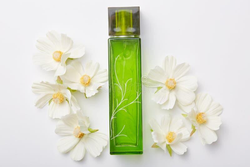 Άρωμα για τις γυναίκες στο πράσινο μπουκάλι και τα λουλούδια γύρω από απομονωμένος πέρα από το άσπρο υπόβαθρο Ευχάριστη aromat ή  στοκ φωτογραφίες