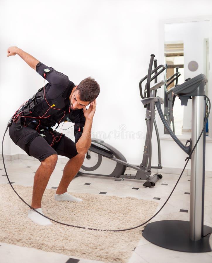 Άσκηση ατόμων κορμός-που κάμπτει με τη συστροφή, στην ηλεκτρο μυϊκή ΕΤΠ στοκ φωτογραφία με δικαίωμα ελεύθερης χρήσης