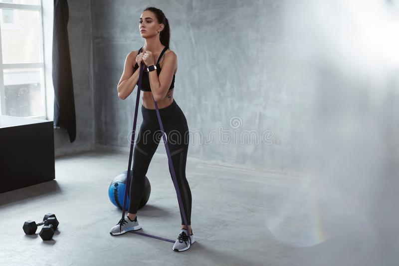 Άσκηση ικανότητας Αθλήτρια που ασκεί με τη ζώνη αντίστασης στοκ εικόνα