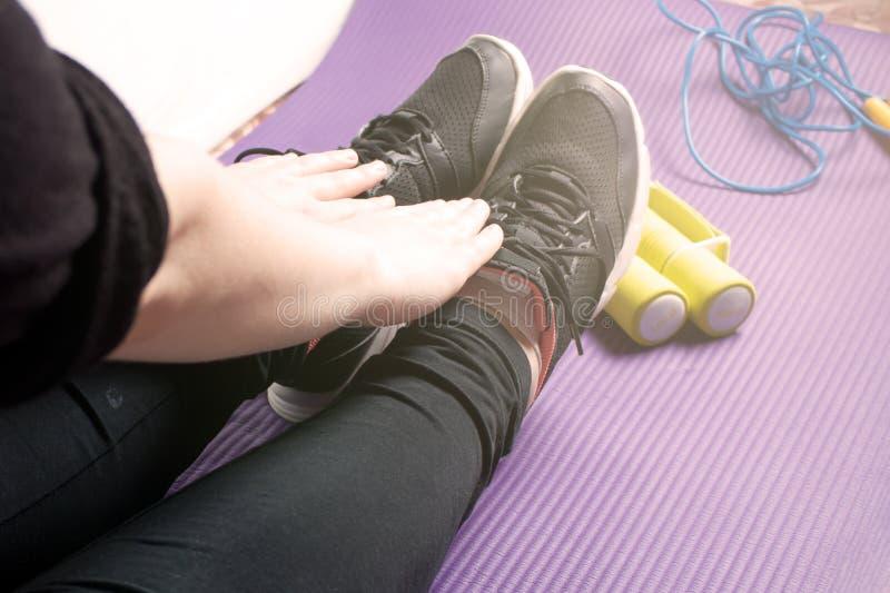 Άσκηση πρωινού σε ένα χαλί γιόγκας με τους αλτήρες και ένα πηδώντας σχοινί, άσκηση στοκ φωτογραφία με δικαίωμα ελεύθερης χρήσης