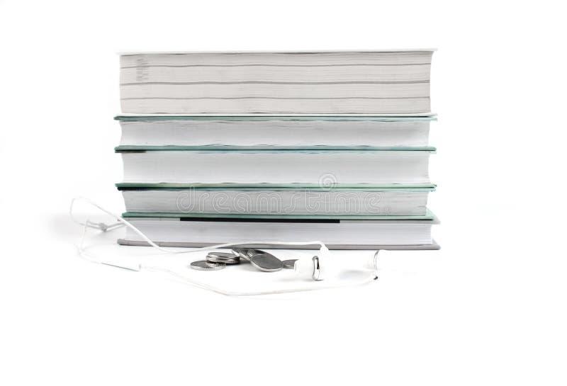 Άσπρα ακουστικά και νομίσματα κοντά στο σωρό των βιβλίων Έννοια των φτηνών ακουστικών βιβλίων Άσπρο υπόβαθρο με το copyspace για  στοκ φωτογραφίες