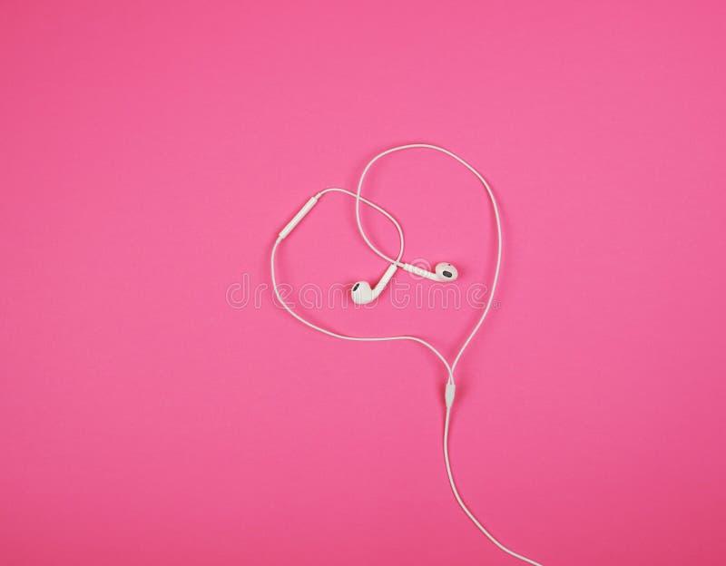 άσπρα ακουστικά με ένα καλώδιο σε ένα ρόδινο υπόβαθρο στοκ εικόνες