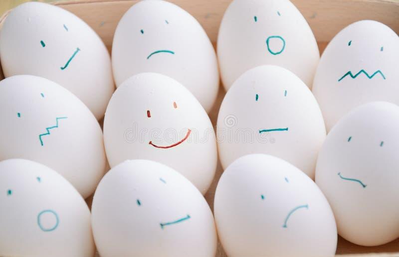 Άσπρα αυγά με τις διαφορετικές συγκινήσεις στο δίσκο οριζόντιο στοκ εικόνα