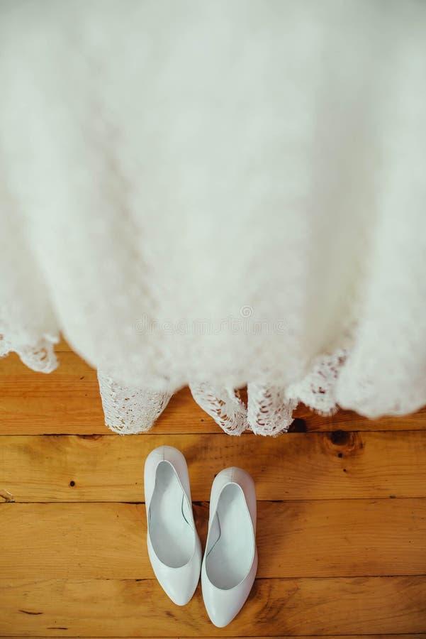 Άσπρα γαμήλια παπούτσια και φόρεμα στο ξύλινο υπόβαθρο στοκ φωτογραφίες