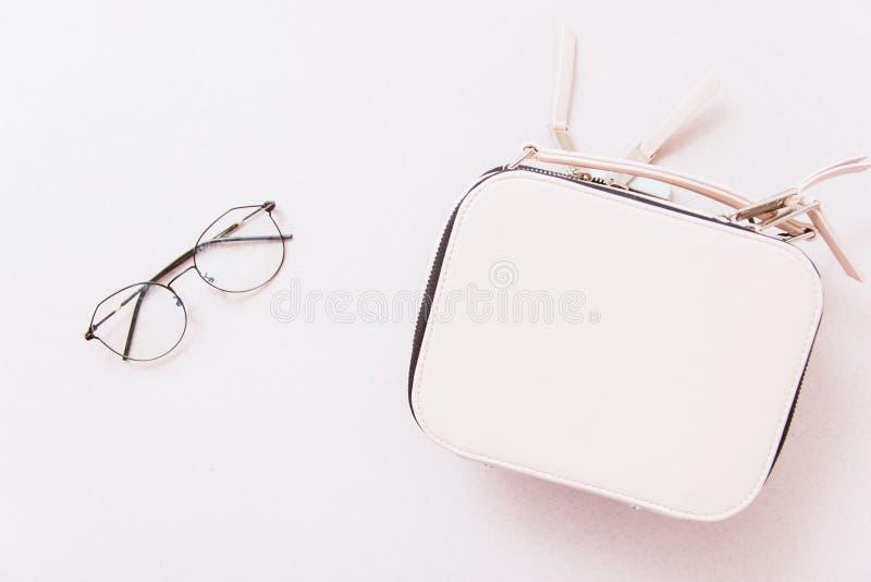 Άσπρα γυαλιά τσαντών και εικόνας σε ένα μπεζ υπόβαθρο στοκ εικόνες