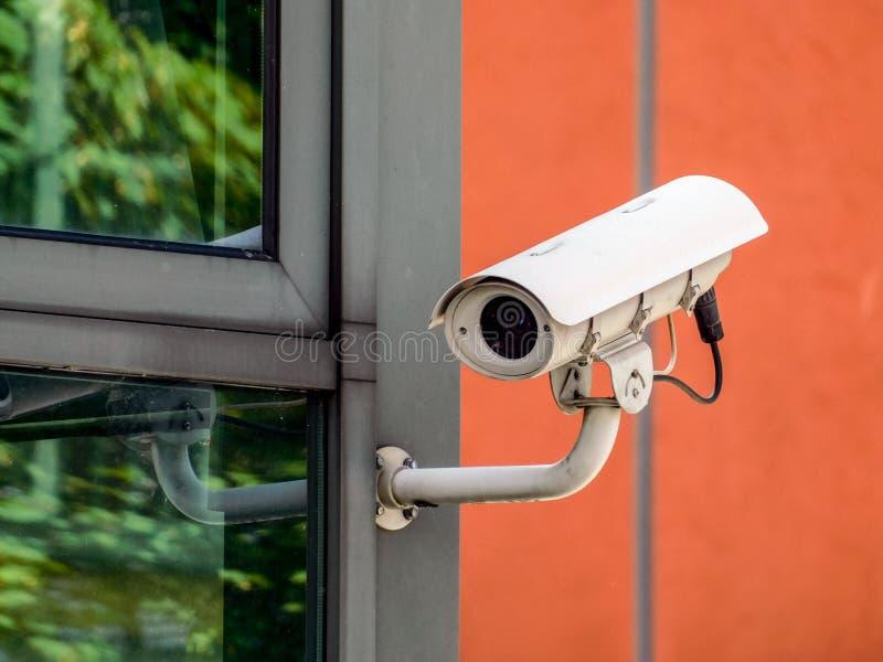 Άσπρα κάμερα ασφαλείας CCTV που ελέγχουν όλα γύρω από το κτήριο στοκ εικόνα
