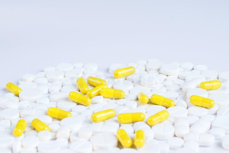 Άσπρα και κίτρινα χάπια σε ένα άσπρο υπόβαθρο στοκ εικόνα