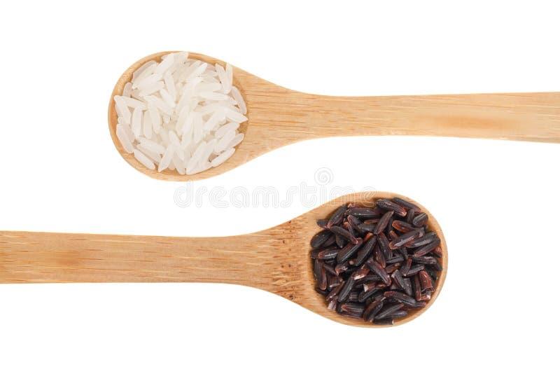 Άσπρα και μαύρα σιτάρια ρυζιού στο ξύλινο κουτάλι που απομονώνεται στο άσπρο υπόβαθρο Τοπ όψη Επίπεδος βάλτε στοκ φωτογραφία