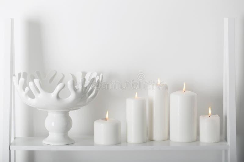 Άσπρα κεριά που καίνε σε ένα ράφι στοκ φωτογραφίες με δικαίωμα ελεύθερης χρήσης