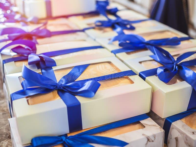 Άσπρα κιβώτια δώρων αναμνηστικών με τις μπλε κορδέλλες στοκ φωτογραφία