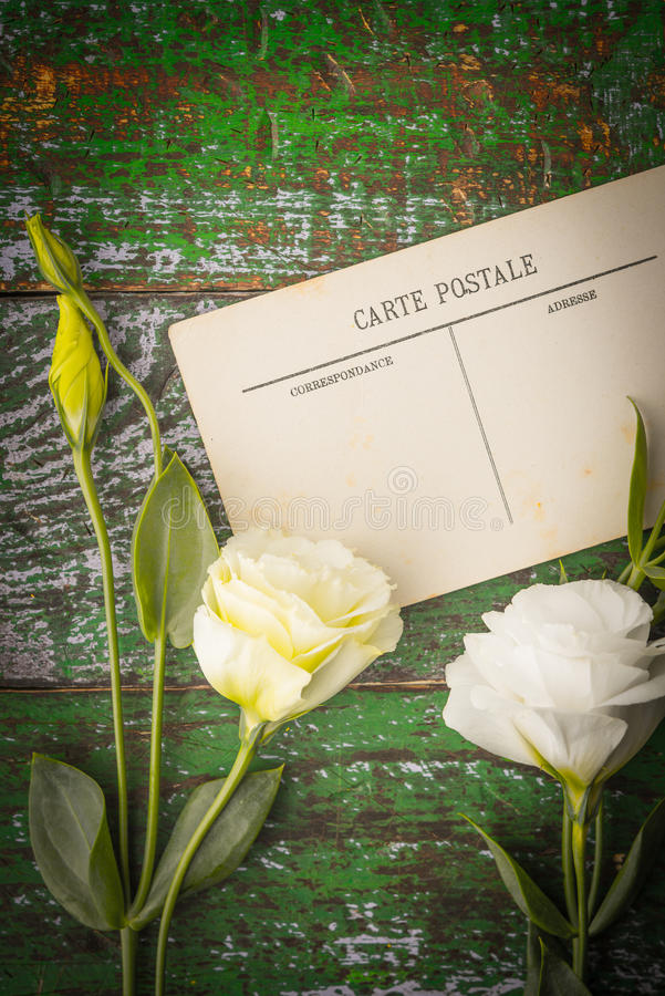 Άσπρα λουλούδια με την κάρτα στην ξύλινη επιτραπέζια κατακόρυφο στοκ εικόνες με δικαίωμα ελεύθερης χρήσης