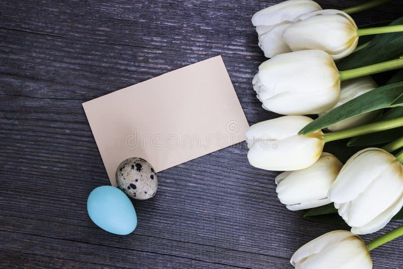 Άσπρα λουλούδια τουλιπών ανθοδεσμών με με τα αυγά Πάσχας egs σε ξύλινο στοκ φωτογραφία