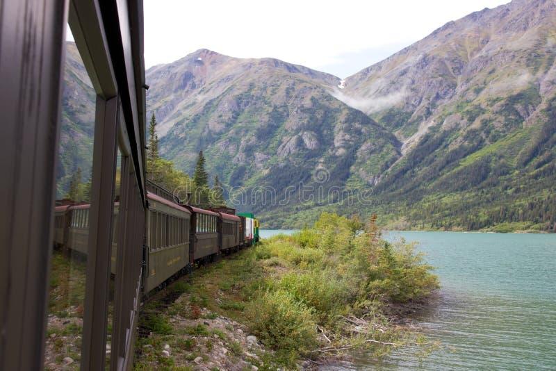 Άσπρα πέρασμα και τραίνο σιδηροδρόμων διαδρομών Yukon κατά μήκος της λίμνης του Bennett στοκ φωτογραφία