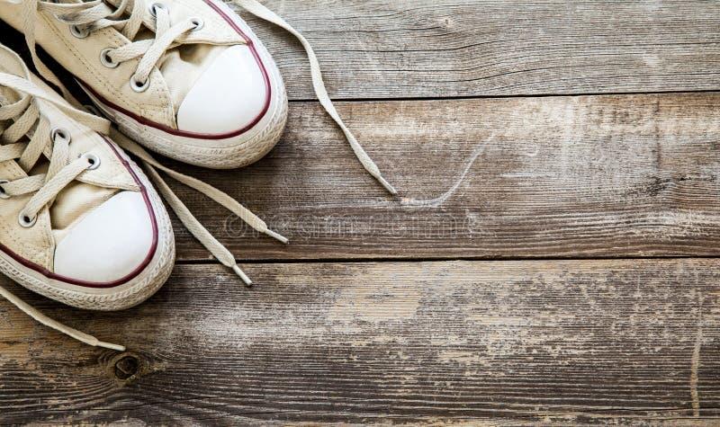 Άσπρα παπούτσια καμβά στο ξύλινο υπόβαθρο διάστημα αντιγράφων στοκ εικόνες
