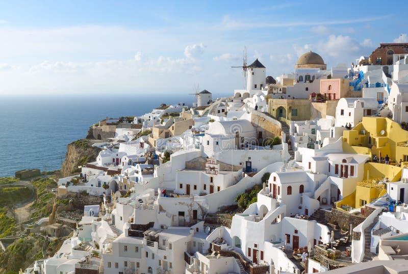 Άσπρα παραδοσιακά ελληνικά σπίτια σε μια βουνοπλαγιά στο νησί Santorini Οι τουρίστες περιμένουν το ηλιοβασίλεμα στοκ εικόνα