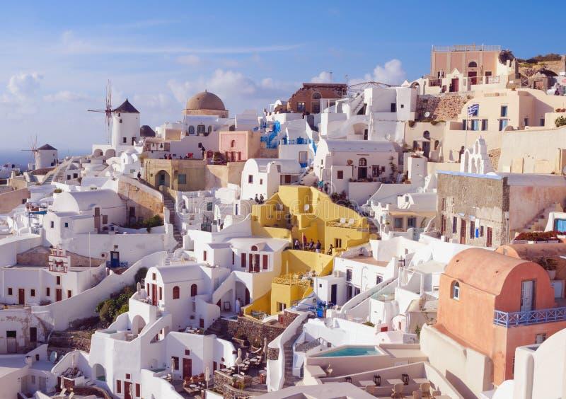 Άσπρα παραδοσιακά ελληνικά σπίτια σε μια βουνοπλαγιά στο νησί Santorini Οι τουρίστες περιμένουν το ηλιοβασίλεμα στοκ φωτογραφίες