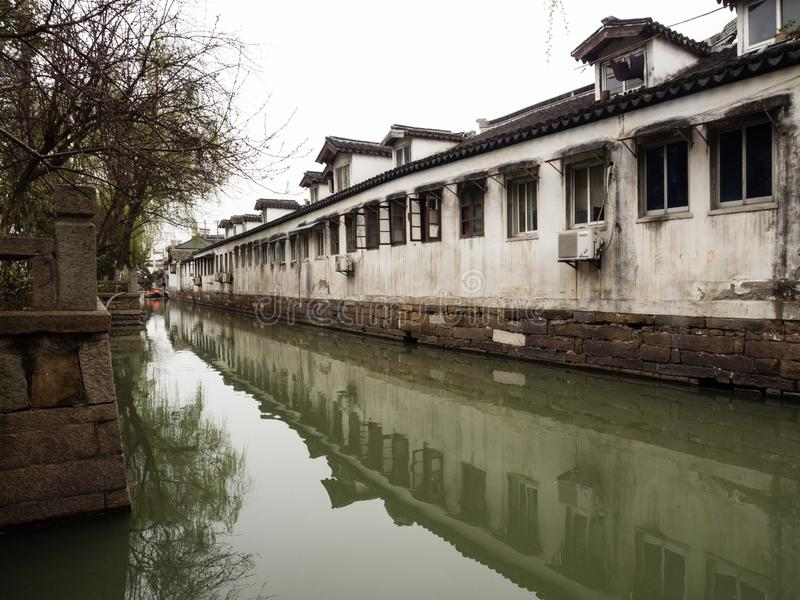 Άσπρα περιτοιχισμένα σπίτια που απεικονίζονται στα νερά καναλιών σε ιστορικό στο κέντρο της πόλης Suzhou στοκ εικόνα