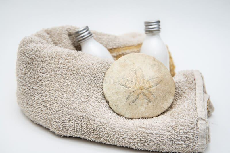 Άσπρα πετσέτα μπουκαλιών λοσιόν και δολάριο άμμου στοκ εικόνα