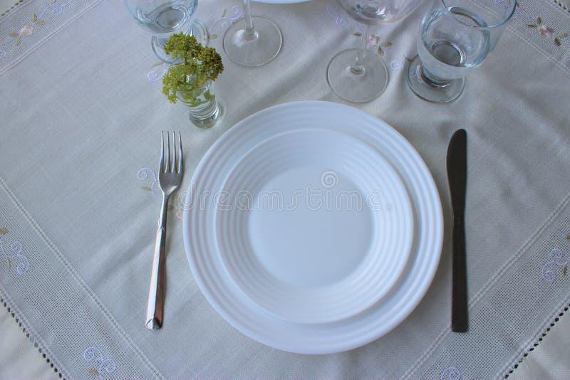 Άσπρα πιάτα, συσκευές, γυαλιά σε ένα άσπρο τραπεζομάντιλο κορυφαία όψη στοκ φωτογραφία