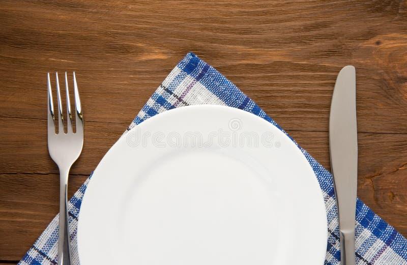 Άσπρα πιάτο, μαχαίρι και δίκρανο στο ξύλο στοκ εικόνα με δικαίωμα ελεύθερης χρήσης