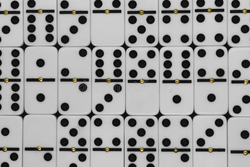 Άσπρα πλαστικά ντόμινο με τη μαύρη επιφάνεια υποβάθρου σημείων και με τα χρυσά σημεία μετάλλων στη μέση κάθε ντόμινο στοκ εικόνες με δικαίωμα ελεύθερης χρήσης