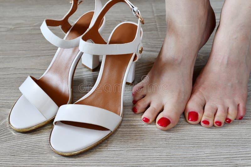 Άσπρα σανδάλια γυναικών πόδια και στοκ εικόνα με δικαίωμα ελεύθερης χρήσης