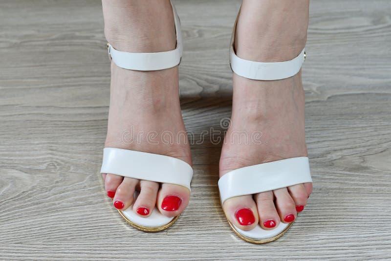 Άσπρα σανδάλια γυναικών πόδια και στοκ φωτογραφία με δικαίωμα ελεύθερης χρήσης