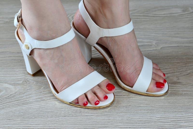 Άσπρα σανδάλια γυναικών πόδια και στοκ εικόνες