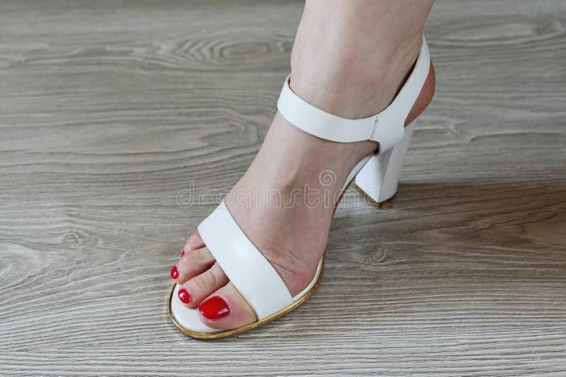Άσπρα σανδάλια γυναικών πόδια και στοκ φωτογραφία