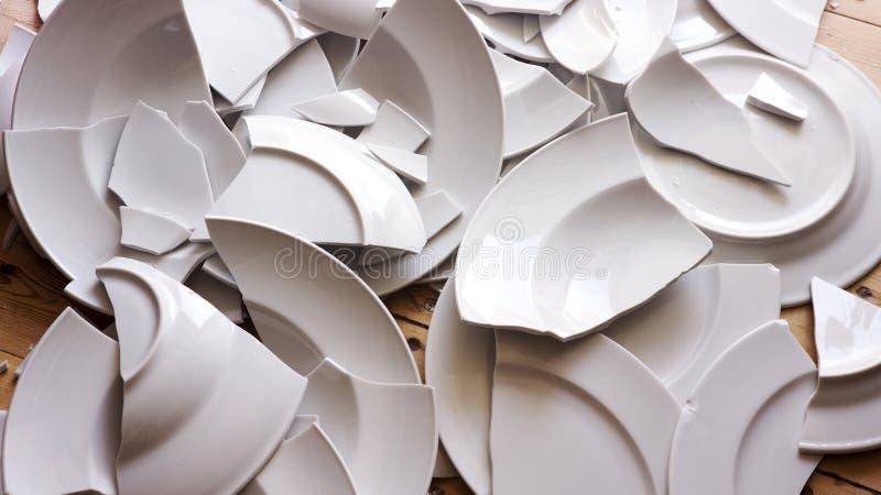 Άσπρα σπασμένα πιάτα σε ένα ξύλινο πάτωμα στοκ φωτογραφίες με δικαίωμα ελεύθερης χρήσης