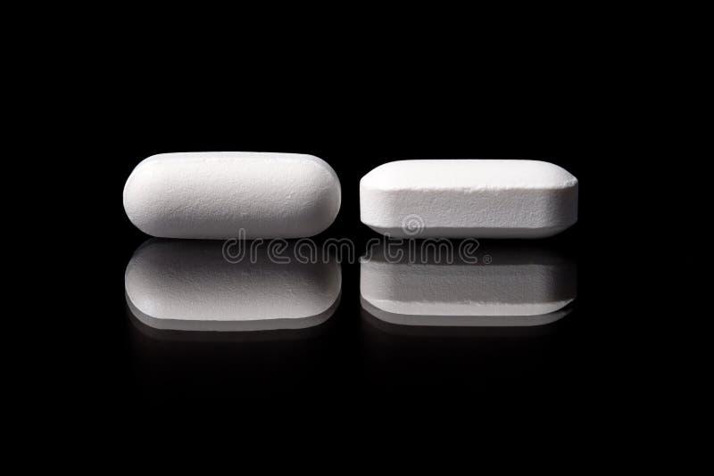 Άσπρα στενόμακρα φαρμακευτικά χάπια στο μαύρο υπόβαθρο στοκ εικόνες