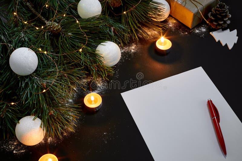 Άσπρα σφαίρες και σημειωματάριο Χριστουγέννων που βρίσκονται κοντά στον πράσινο κομψό κλάδο στη μαύρη τοπ άποψη υποβάθρου Διάστημ στοκ εικόνα