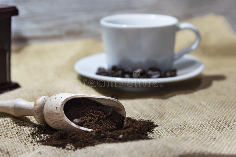 Άσπρα φλυτζάνι και πιάτο με τα φασόλια, τον αλέθοντας καφέ και έναν ξύλινο μύλο στο αγροτικό υπόβαθρο στοκ εικόνες