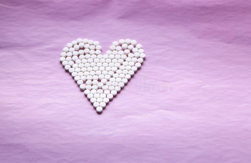 Άσπρα χάπια που σχεδιάζονται με μορφή μιας καρδιάς σε ένα ρόδινο υπόβαθρο έννοια - καρδιακές παθήσεις, αναταραχές καρδιών και φάρ στοκ εικόνες