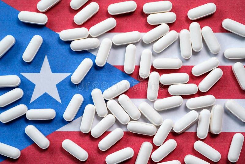 Άσπρα χάπια συνταγών στο υπόβαθρο σημαιών του Πουέρτο Ρίκο στοκ φωτογραφίες