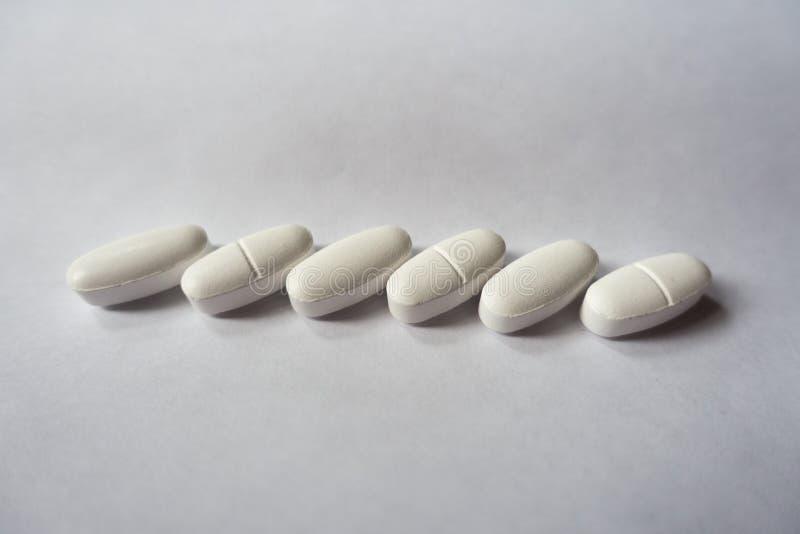 Άσπρα caplets του ασβεστίου σε μια σειρά στοκ εικόνες