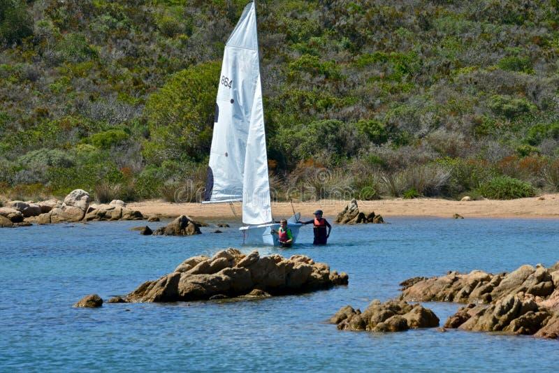 Άσπρες βάρκες πανιών με τους ανθρώπους που μαθαίνουν να πλέει στην μπλε θάλασσα που περιβάλλεται από τη φύση στοκ εικόνα