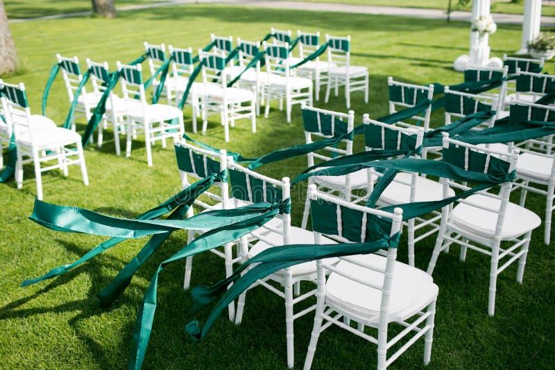Άσπρες γαμήλιες καρέκλες με την πράσινη και σμαραγδένια κορδέλλα υπαίθρια στοκ φωτογραφίες