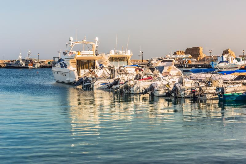 Άσπρες γιοτ και βάρκες στην αποβάθρα στο λιμένα της Πάφος στις ακτίνες του ηλιοβασιλέματος στοκ φωτογραφίες