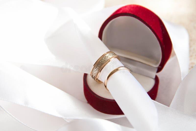 Άσπρες διακοσμήσεις με τα χρυσά γαμήλια δαχτυλίδια στο κιβώτιο στοκ εικόνες