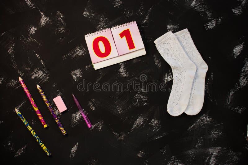 Άσπρες κάλτσες και σχολικές προμήθειες στο μαύρο υπόβαθρο Ο πρώτος του Σεπτεμβρίου E στοκ φωτογραφία