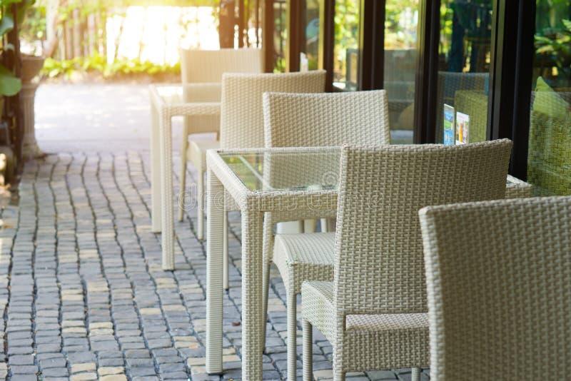 Άσπρες καρέκλα ινδικού καλάμου και επιτραπέζια διακόσμηση στο εστιατόριο, διαδικασία στοκ εικόνες