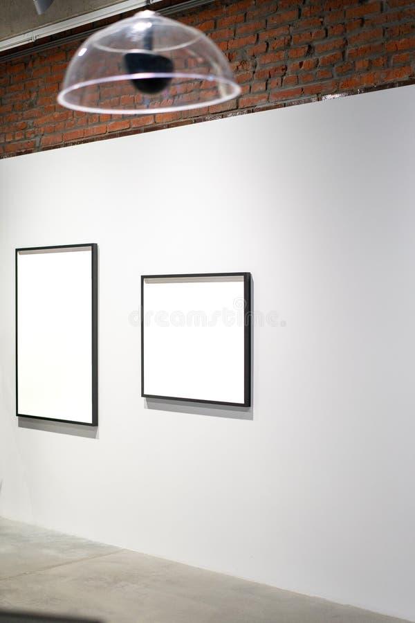 Άσπρες κενές αφίσες καμβά στον τοίχο στο σύγχρονο φωτεινό γκαλερί τέχνης στοκ εικόνα