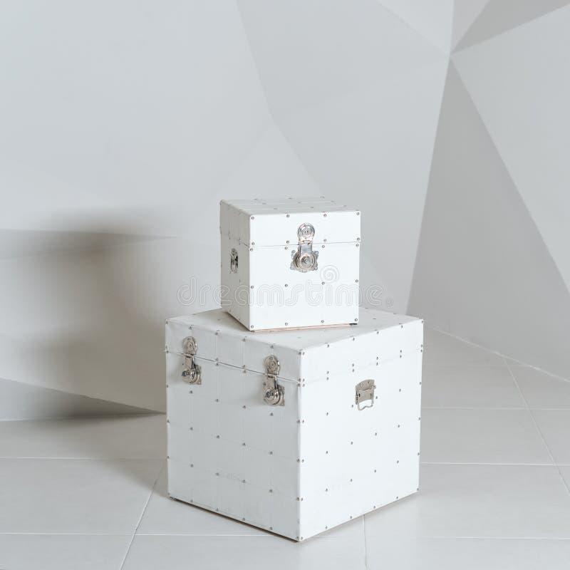 Άσπρες κιβώτια ή βαλίτσες, αποσκευές στο polygonal υπόβαθρο τοίχων στοκ εικόνα