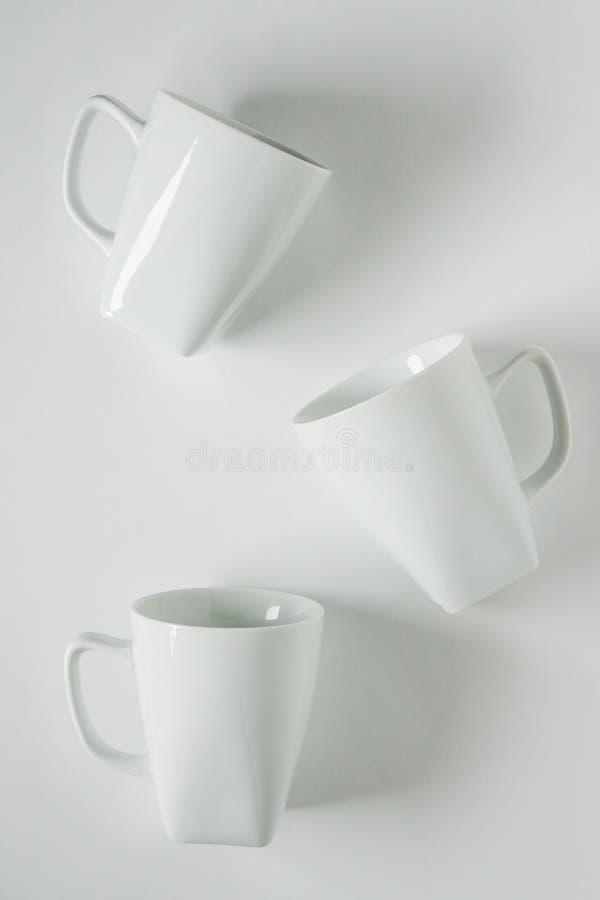 3 άσπρες κούπες καφέ στο άσπρο υπόβαθρο που διασκορπίζεται με το κενό διάστημα αντιγράφων στοκ φωτογραφία με δικαίωμα ελεύθερης χρήσης
